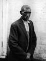 Elderly African American man, wearing overalls, button-up shirt, and suit coat, with white-washed brick wall in background.