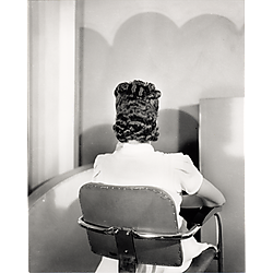 Woman wearing short sleeved white dress, in chair with back to camera modeling hair style, in studio
