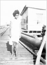 African-American girl walking on railroad tracks, circa late 1930s or early 1940s