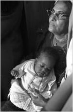 Woman holding a baby, probably listening to Martin Luther King, Jr., speak at a church building in Greenville, Alabama.