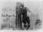 [Spectators looking at charred corpse of Jesse Washington hanging from tree after lynching, Waco, Texas, May 15, 1916]