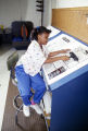 """Eight-year-old Monica Bland working on the paste-up for the """"Kids"""" page of the Tuskegee News at the newspaper's office in Tuskegee, Alabama."""