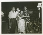 [Vanetta Dillard performs in front of a WANN microphone, three men on stage with her, and large audience looking on.] [Black-and-white photoprint]