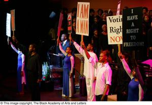 Performers holding signs on stage
