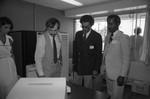 Donald Bohana and David Cunningham, Jr. examine computer operations, Los Angeles, ca. 1978