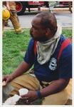 An unidentified, male, African American fire fighter is seated on the ground and eating after helping to extinguish the fire in the Administration / Main Building