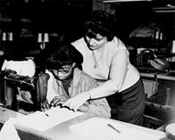 One woman teaches another to sew in a factory, October 21, 1966