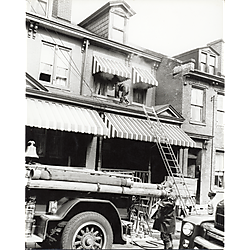 Fire fighter on porch roof with fire truck parked below