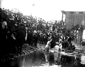 Photograph of a crowd of African Americans engaged in baptism by a river in or near Richmond County, Georgia, late 19th century