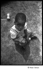 Young child with Pepsi bottle at Jackie Robinson's jazz concert (discarded beer can on the lawn behind)