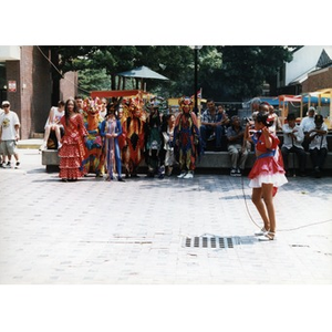 Young girl singing in the plaza at Festival Betances while other young people in costumes look on.