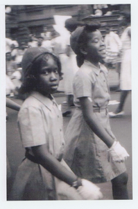 Girls in Brownies uniforms marching in a parade.