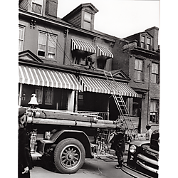 Fire fighter on porch roof of a row house with fire truck parked below