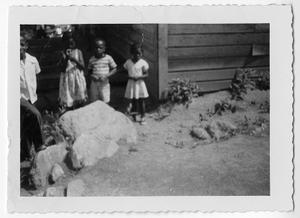 Photograph of African American children standing behind large rocks, Clarkesville, Habersham County, Georgia, 1953