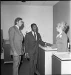 Two men in business suits talking with a woman in an office, Los Angeles, ca. 1973