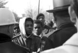 Simuel Schutz, Jr., and other students speaking to policemen who have lined up across Old Montgomery Road to block their demonstration in Tuskegee, Alabama, to protest the murder of Samuel L. Younge, a civil rights worker.