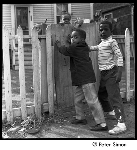 African American children playing by a gate