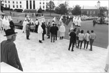 Klansmen and other observers standing in front of the Capitol during a Ku Klux Klan rally in Montgomery, Alabama.