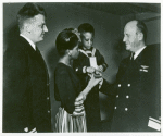 Thumbnail for Mrs. Charles W. David, Jr.; African American widow and her three-year-old son, Neil Adrian receiving the Navy and Marine Corps Medal from Rear Admiral, Stanley V. Parker