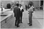 Students gather on campus outside Benson Center, ca. 1965