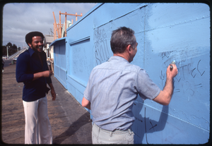 Thumbnail for Bill Withers: Withers laughing with a man cleaning graffiti