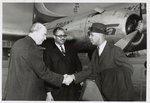 [Roy Wilkins shaking hands Erik Jonsson, mayor of Dallas, Texas, at Love Field International Airport during trip for speaking engagement at Memorial Auditorium as Rev. H. Rhett James, president of the John F. Kennedy NAACP Branch, looks on]