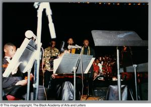Photograph of performers standing on a stage Christmas/Kwanzaa Concert Hallelujah Hip Hop Concert, December 1995