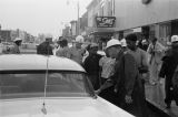 Civil rights demonstrators lined up with police officers beside a parked car during a protest in downtown Gadsden, Alabama.