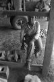 Young woman sitting in a chair inside a barn or shed near Mount Meigs in Montgomery County, Alabama.