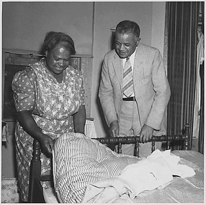 Just one of the million mattresses made by low income-farm families - every mattress made by the family itself of surplus cotton. These are proud possesions in homes where such comfort was unknown before. This Maryland Negro woman shows her mattress to J. B. Pierce, a Federal Negro field agent.