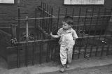 Jasper Wood Collection: Boy in front of iron fence