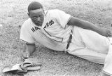 Baseball player lying on the grass during a game played by teams of an amateur baseball league in Montgomery, Alabama.