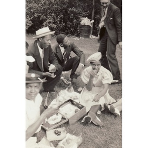 A group of men and women enjoy a picnic in the park.
