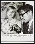 Singer Sammy Davis Jr. holds the hand of his bride, actress May Britt, showing the gold wedding band he gave her, for all to see The couple were married in private ceremonies at the negro singer's home 11/13.
