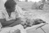 Woman and little girl on a cot in the dirt yard in front of the tent where they are living in Lowndes County, Alabama.