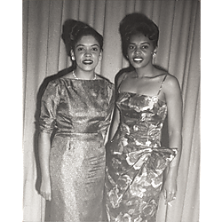 Two women in evening dress, one holding cigarette