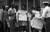 Police officer taking signs from adolescent civil rights demonstrators who had been marching down a sidewalk during the Children's Crusade in Birmingham, Alabama.