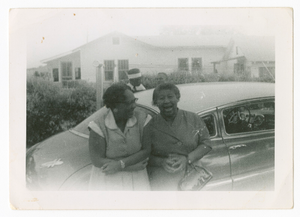 Photographic print of two women standing in front of a car, with two men behind
