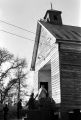 People entering a wooden church building in rural Prattville, Alabama, probably for a meeting of the Autauga County Voters Association.