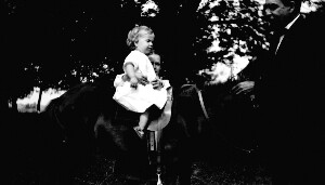 Unidentified man and child on horse.