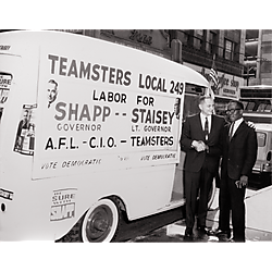 Milton Shapp shaking hands with another man beside a campaign van advertising labor support for Shapp for Governor, Staisey for Lieutenant Governor in front of the Penn Theater and Mayflower Coffee Shop