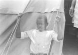 Boy leaning back against the outside of the tent where his family is living in Lowndes County, Alabama.