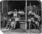Conference[?], Harper's Ferry, West Virginia, ca. 1915. Jesse Moorland on left sitting on steps holding cap; William Hunton is two rows above Moorland wearing hat; Max Yergan is on the right, leaning against post; Channing Tobias sitting on right step...