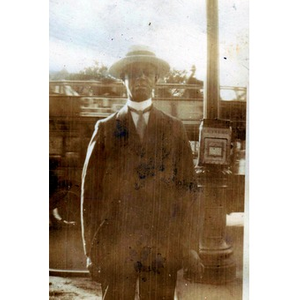 African American man standing outside next to a letter box
