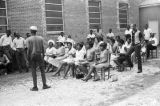 Man standing in front of an audience outside a brick church building in Prattville, Alabama, during a meeting of the Autauga County Improvement Association.