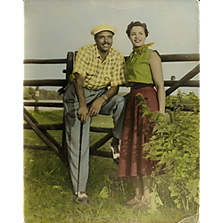 Man and woman posing outdoors before wood fence