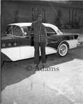 Young man next to motor vehicle, Los Angeles, 1956