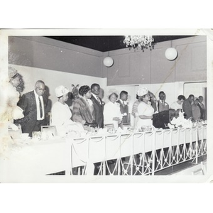 People stand at a long banquet table.