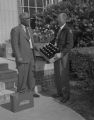 Mr. Ware of the Coca-Cola Bottling Company in Montgomery, Alabama, presenting a case of drinks to the dean of men at the junior college department of the Alabama State College for Negroes.