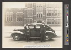 African American couple posed in front of Ford sedan